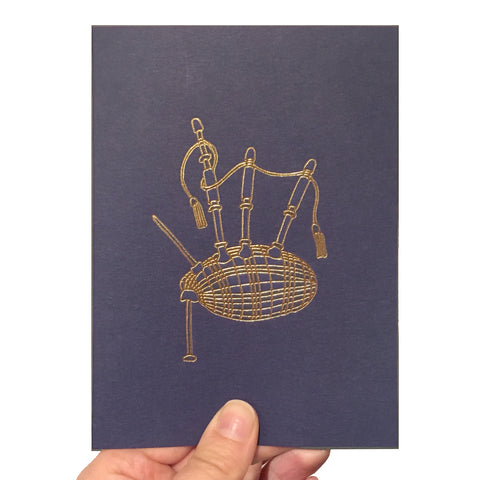 Navy blue card with a gold foiled bagpipe illustration