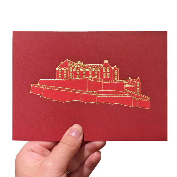 Red greeting card with a gold foiled illustration of Edinburgh Castle