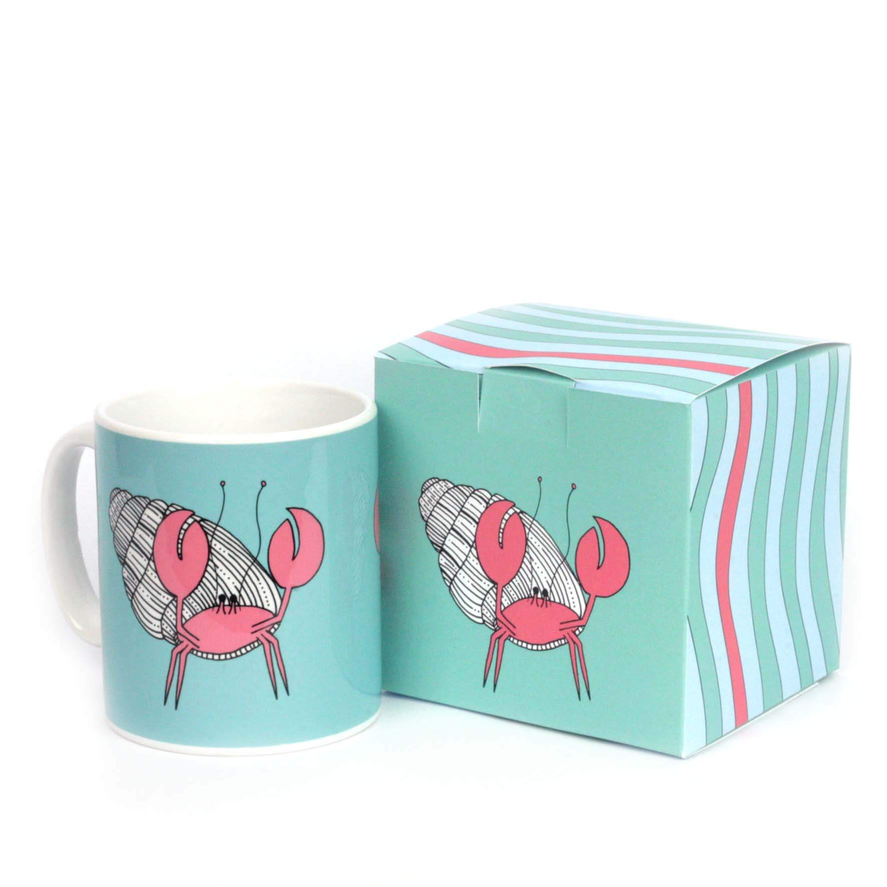Turquoise mug with gift box featuring an illustration of a hermit crab