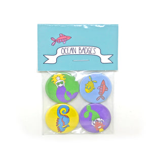 A set of four ocean badges featuring fish, a seahorse and mermaid