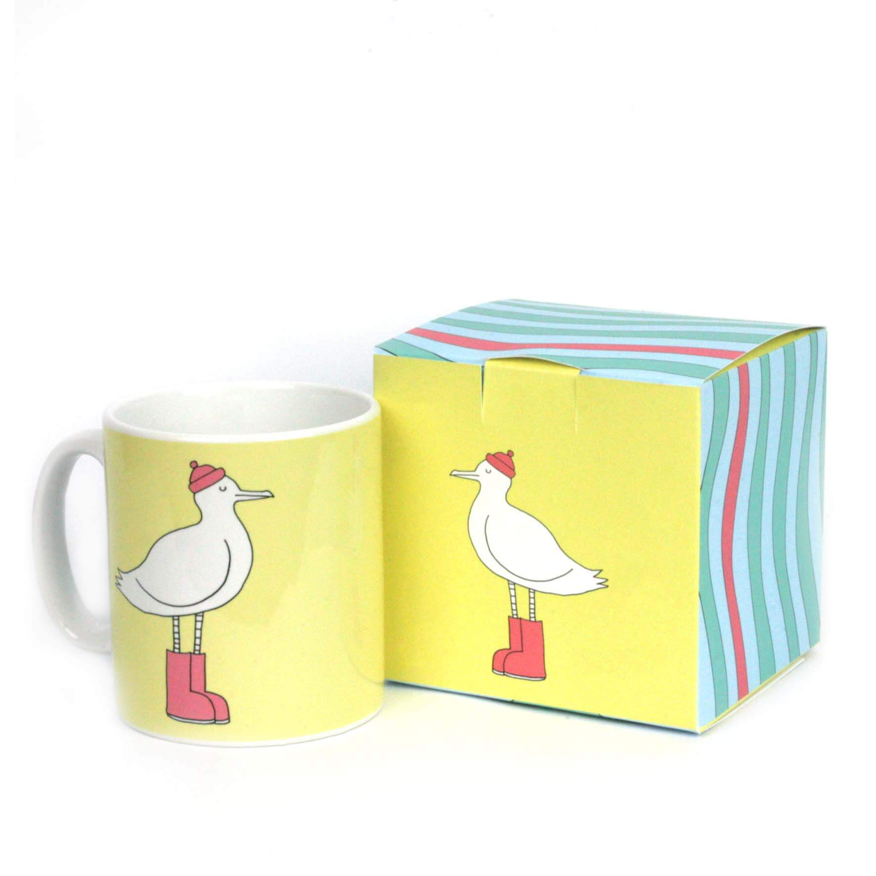 Yellow mug with gift box featuring an illustration of a seagull