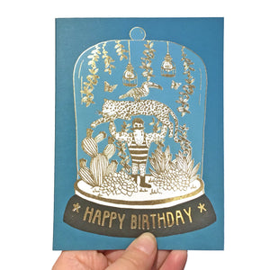 Blue birthday card featuring a strongman in a bell jar