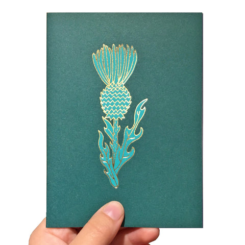 Green card with a gold foil thistle design