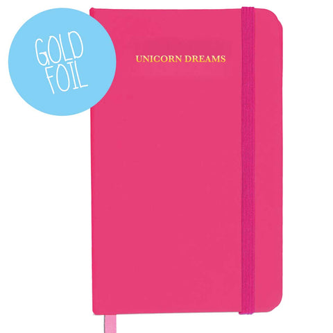 Pink leather like notebook with the words 'unicorn dreams' written in gold