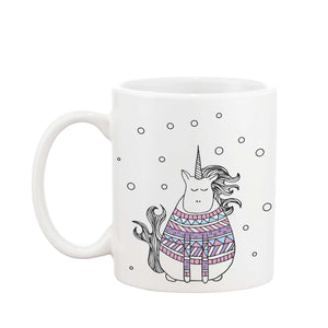 White mug with an illustration of a unicorn wearing a Christmas jumper