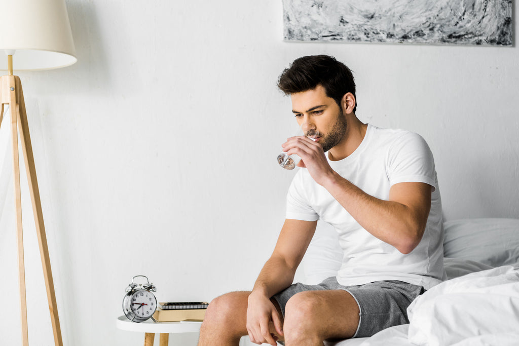 Man drinking water while sitting on a bed