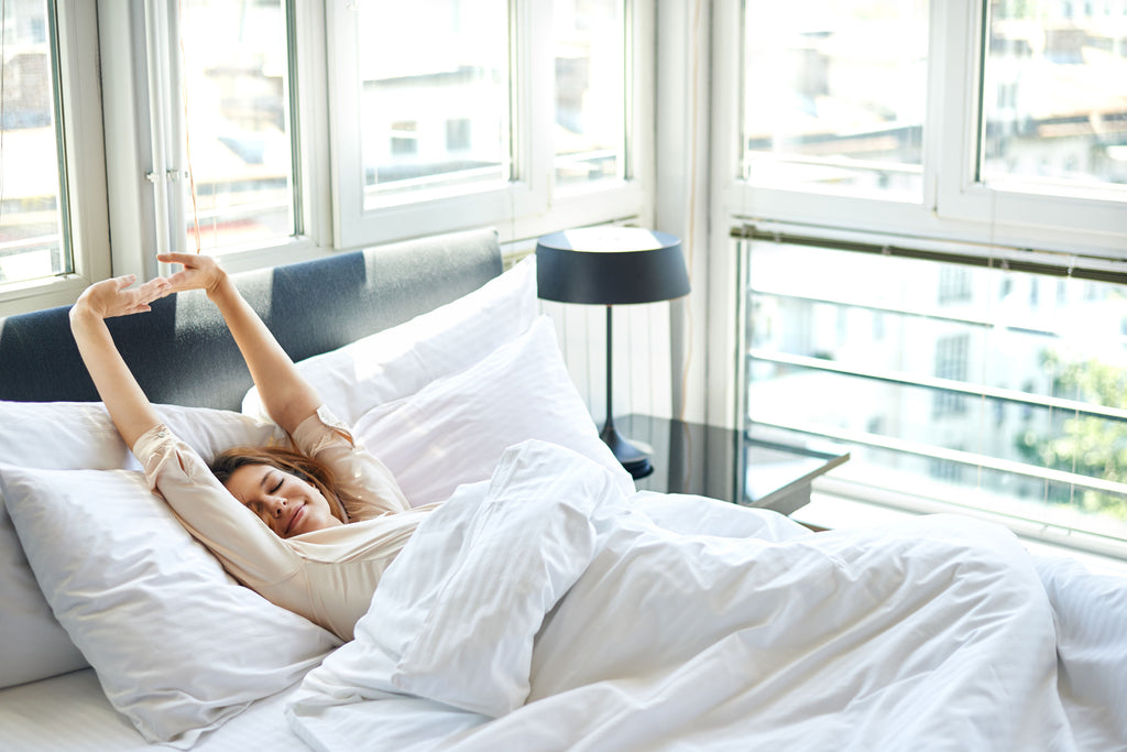 Woman waking up feeling refreshed next to auto blinds and window