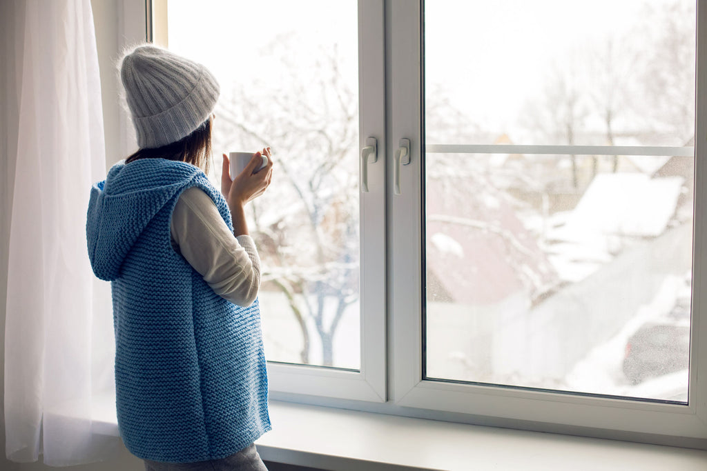 Woman drinking coffee and watching snowfall from window