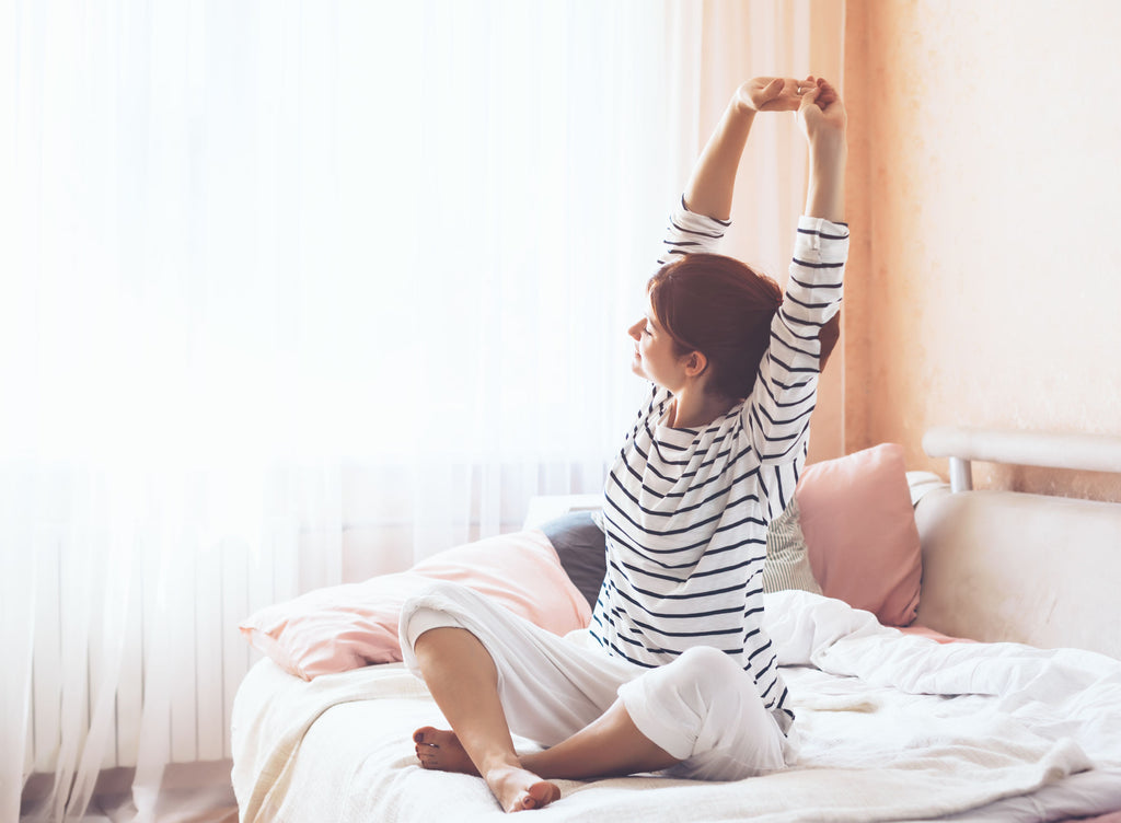 Woman stretching in bed with open smart window blinds
