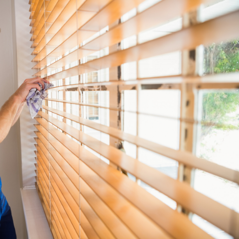 Cleaning window blinds with damp cloth