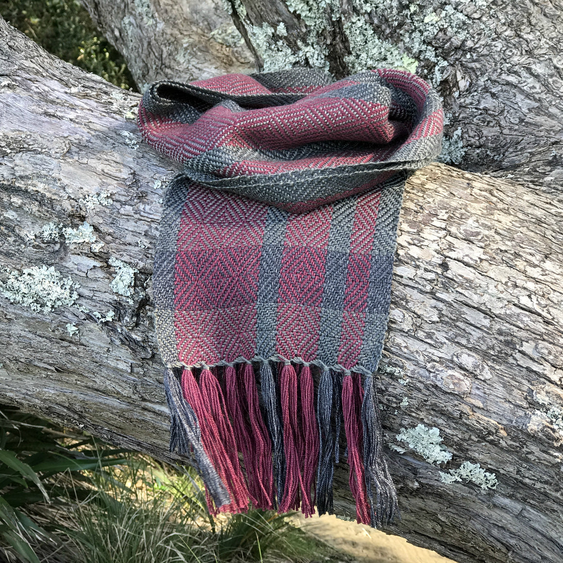 Silky soft handwoven alpaca scarf featuring a sophisticated twill diamond pattern in burgundy tones of charcoal grey and merlot.
