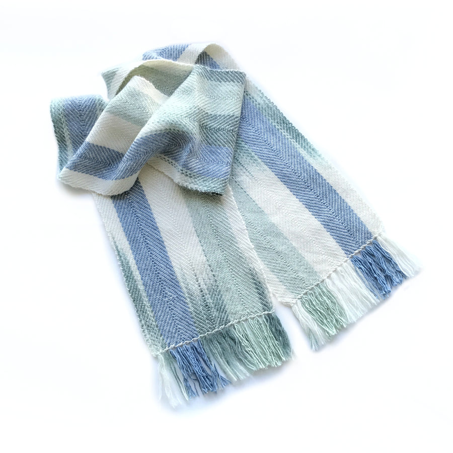 A limited edition scarf handwoven from luxurious alpaca, silk and merino wool, featuring hand-dyed pools of colour in blue and green.