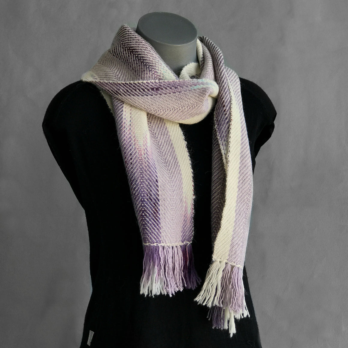 A limited edition scarf handwoven from luxurious alpaca, silk and merino wool, featuring hand-dyed pools of colour in lavender and mauve.
