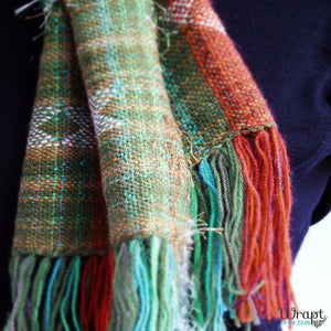 Detail of a long scarf handwoven in New Zealand in green, brown and orange, inspired by the native Kea bird