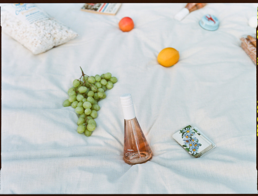 Biodynamic wine: Usual Wines Rose on a picnic blanket with various objects