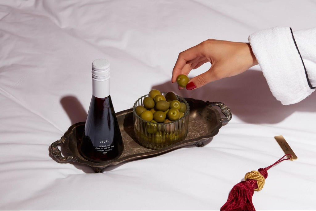 sweet red wine: person grabbing an olive from a bowl placed in a platter with a bottle of red wine from Usual Wines