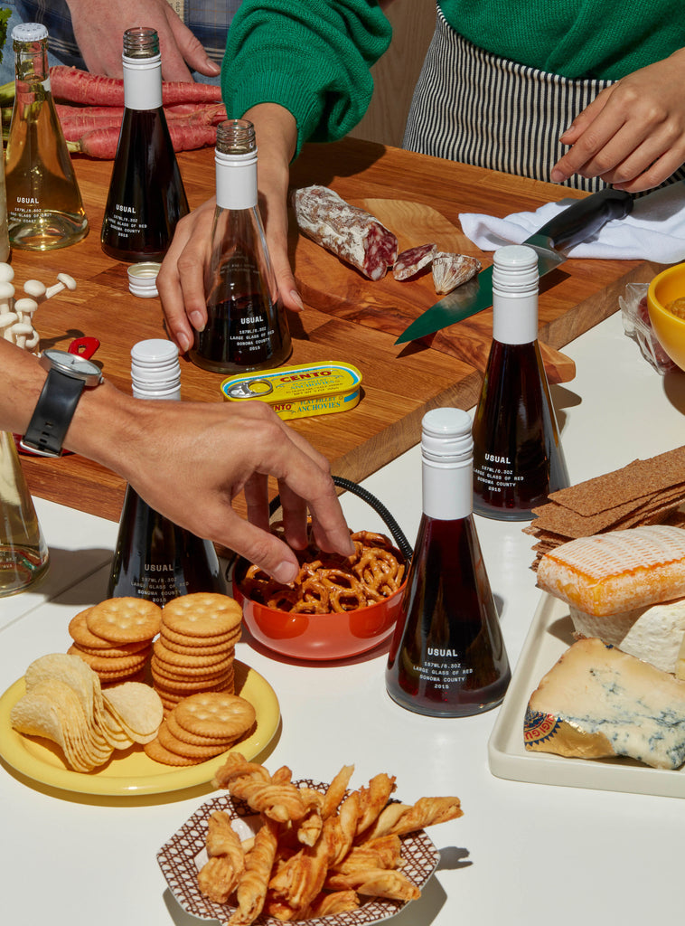 An outdoor wine tasting party with plates of appetizers