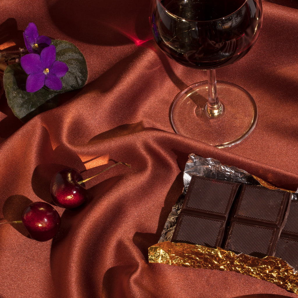 A glass of red wine with cherries and chocolate