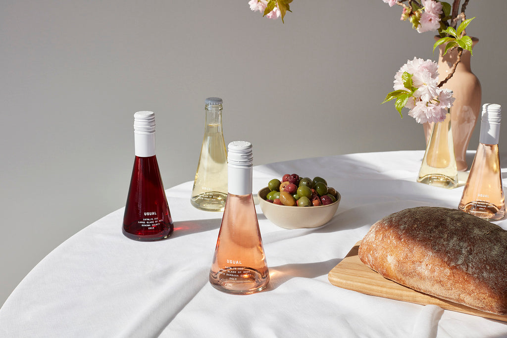 five Usual Wines bottles with bread and grapes on a table