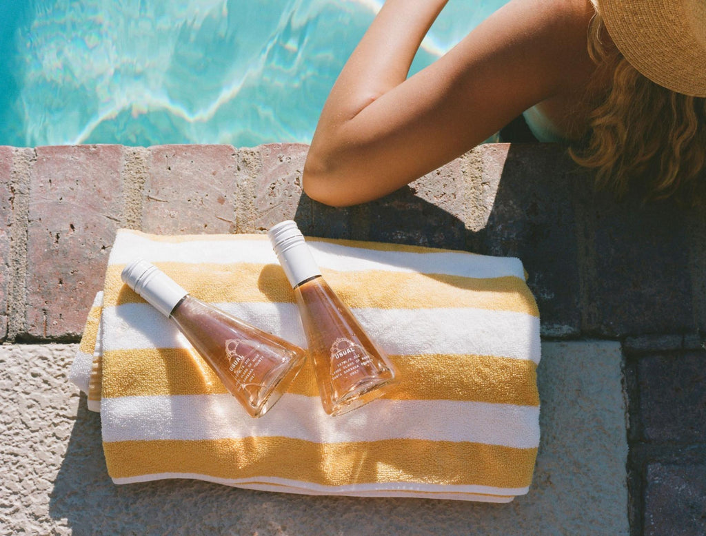 woman by the poolside with two bottles of Rosé from Usual Wines
