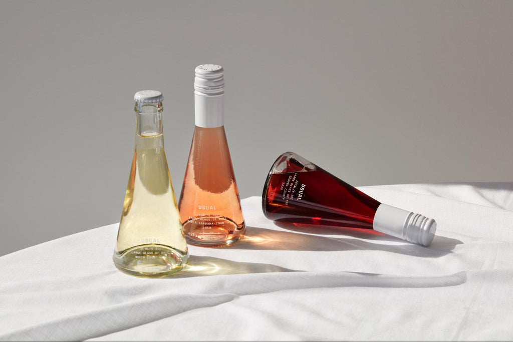 wine decanter: Three wine bottles on top of table