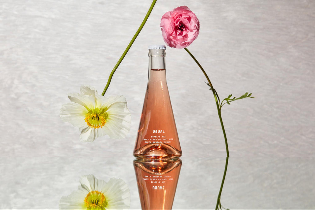 Rose wine with two flowers leaning on bottle