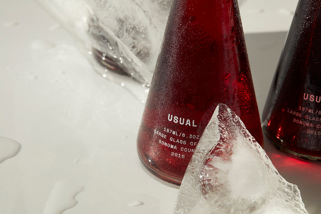 Two bottles of USUAL Red with blocks of ice around them