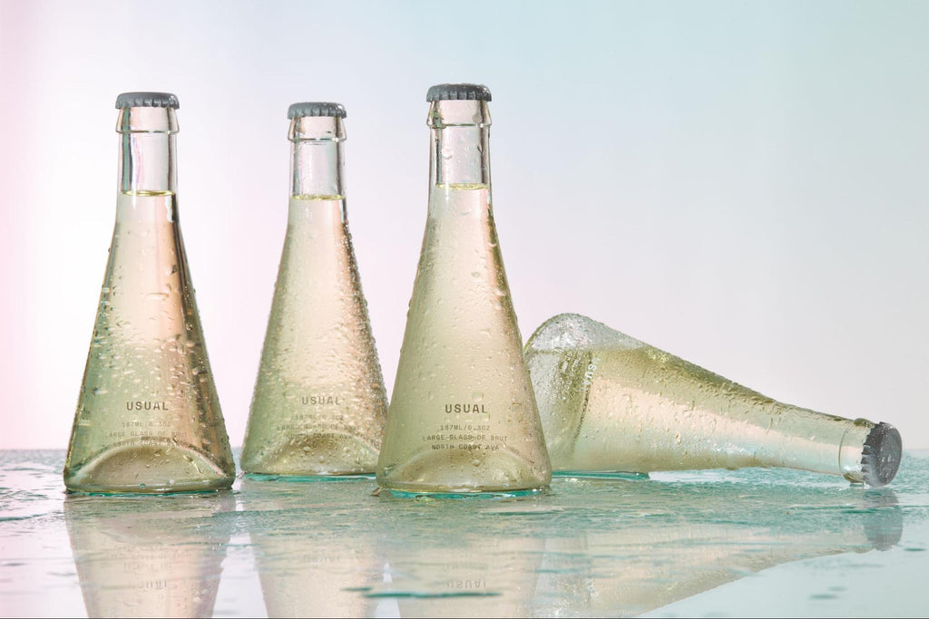 Four Usual Brut bottles on a glass surface