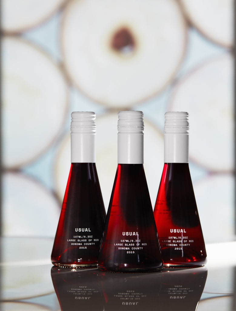 Gamay wine: Three bottles of USUAL Red Blend on top of a glass surface