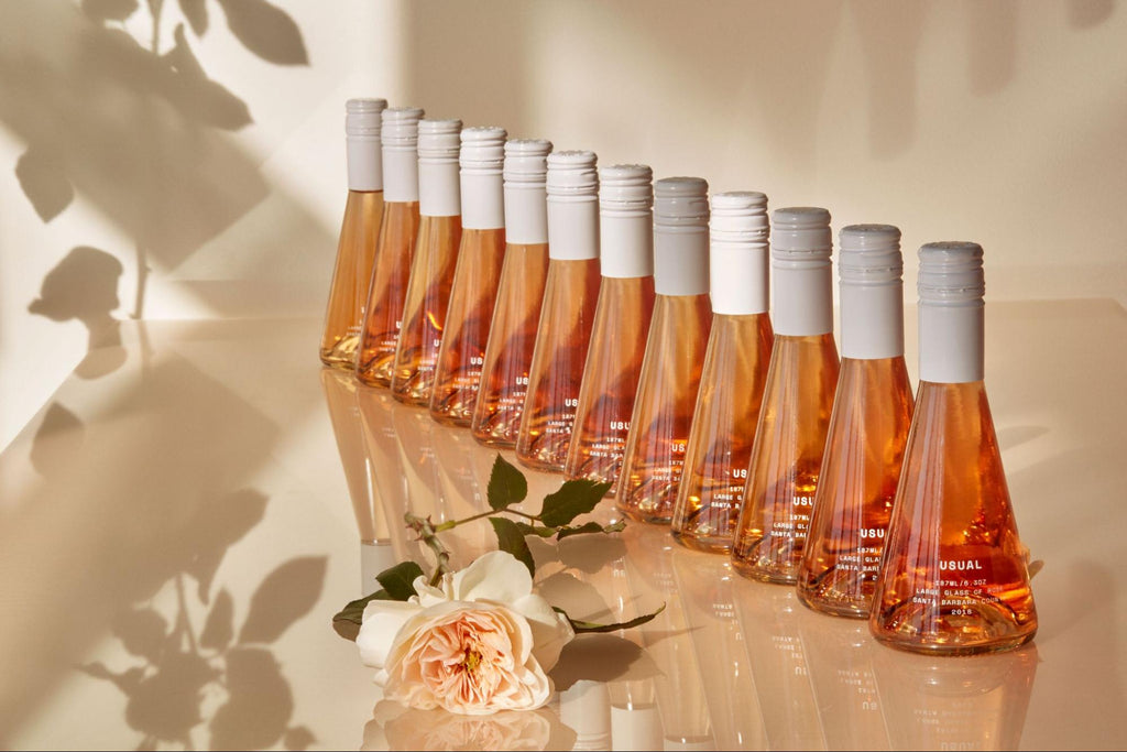 large bottles of Rosé from Usual Wines lined up beside a pink rose