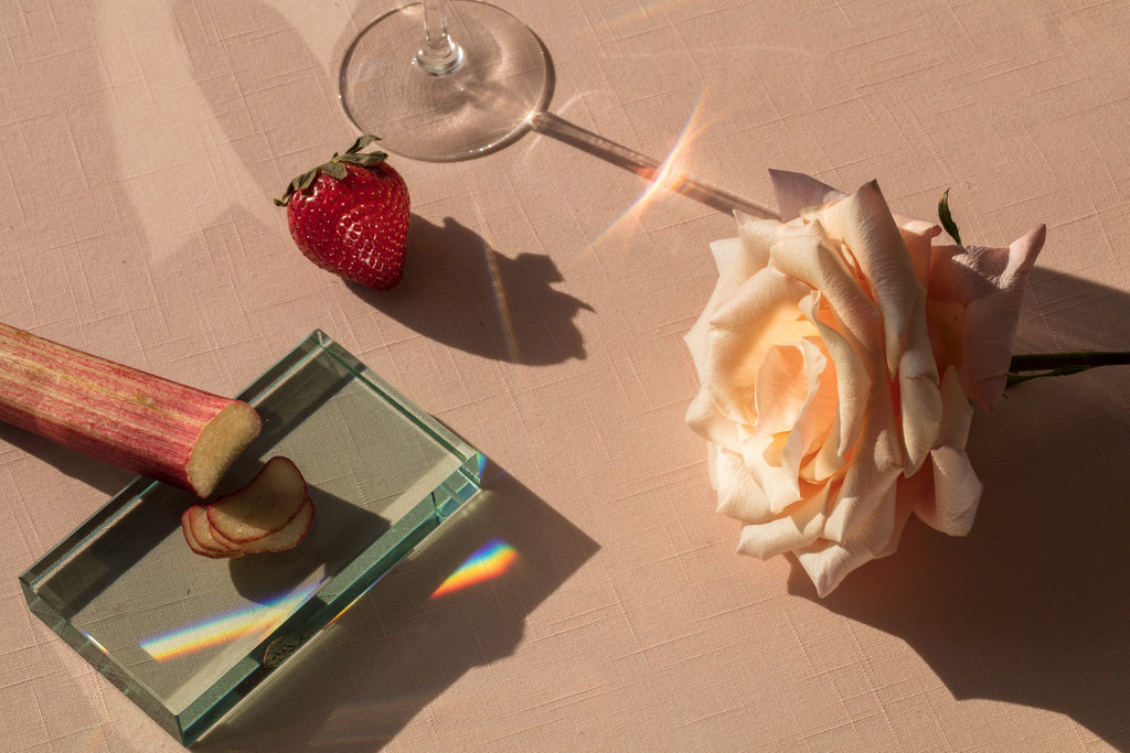 holding wine glass: rose, strawberry and wine glass on the table