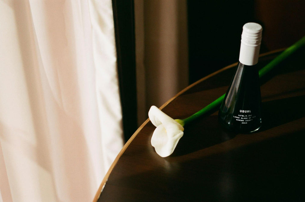 bottle of red wine from Usual Wines with a white rose on the table