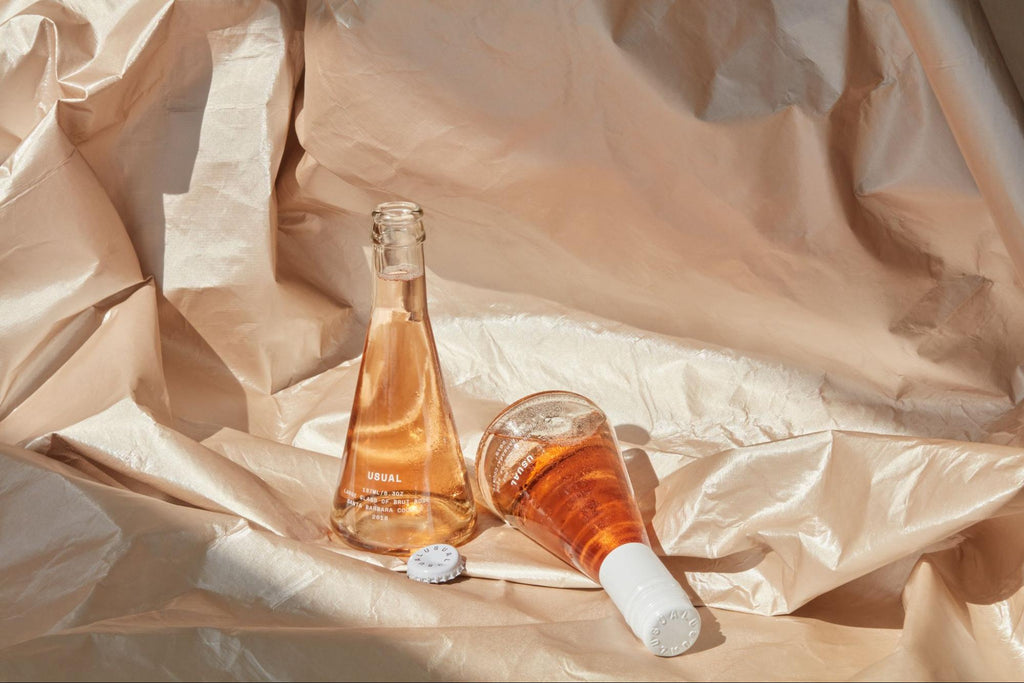 wine gift basket ideas: Two Usual Wines bottles placed on top of fabric