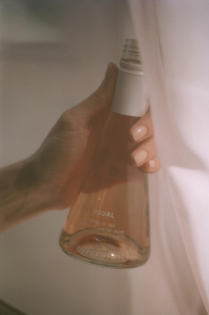 person holding a Usual Wines bottle