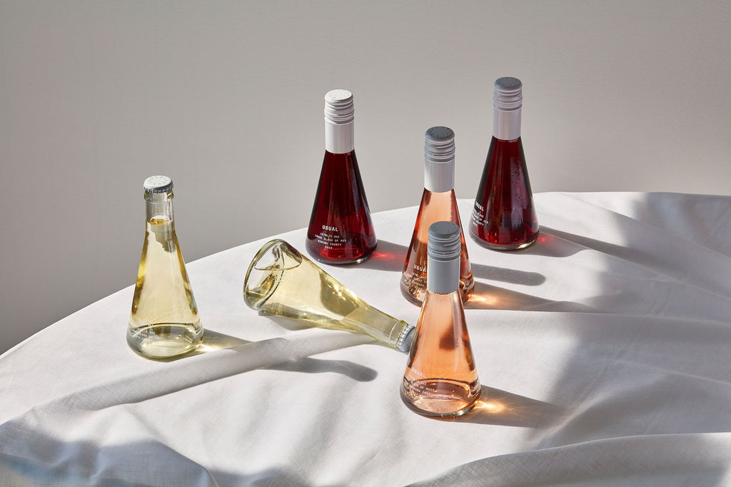 Six Usual Wines bottles on a table
