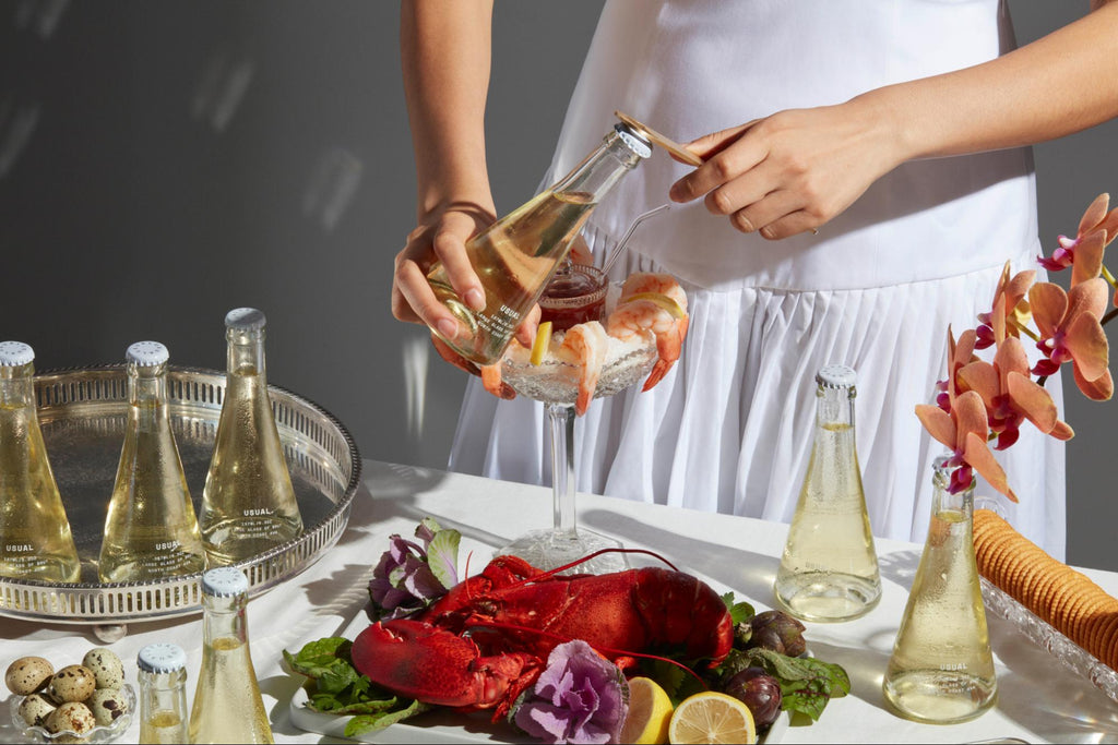 Person pops bottle cap off Usual Wines, standing in front of seafood spread