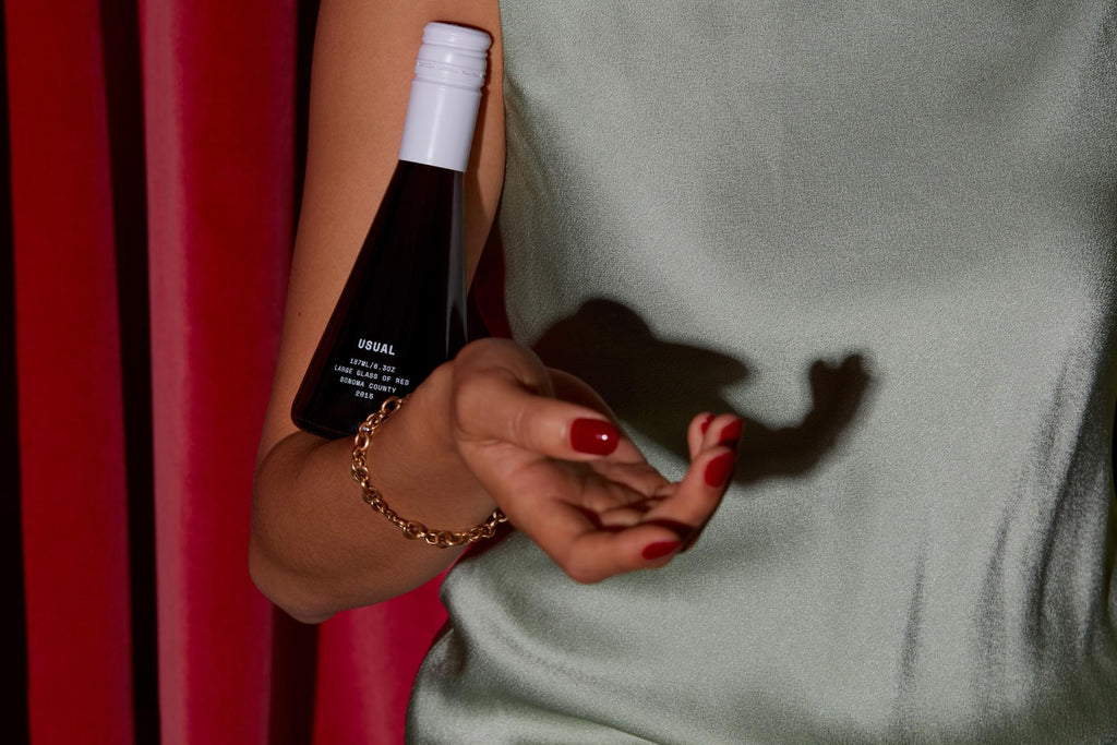 Woman holds Usual Wines bottle in crook of arm