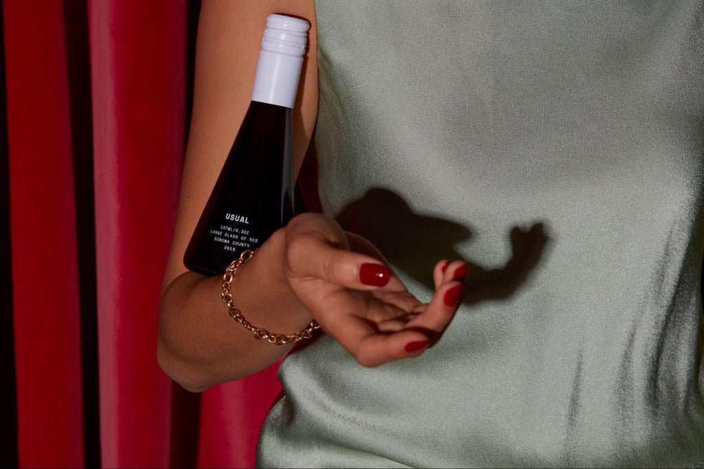 person with a bottle of red wine from Usual Wines on their arm