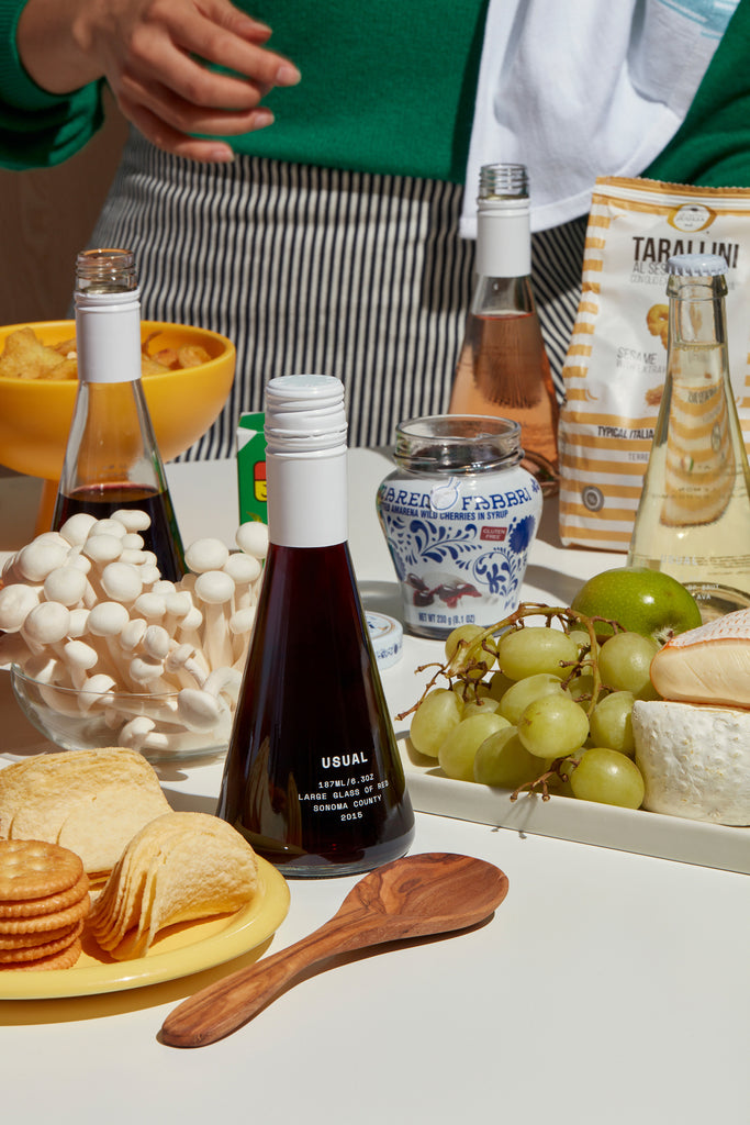 A table spread with wine and cheese and other snacks
