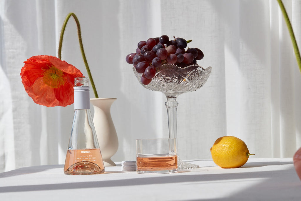 Wine without sulfites: Usual Wines rose next to grapes and lemon