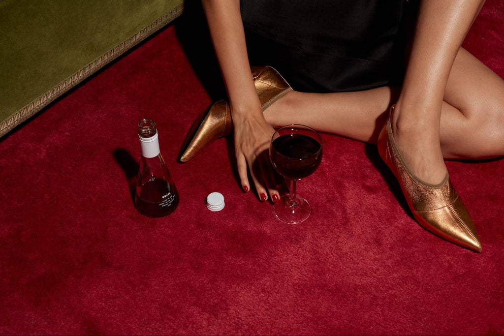 woman sitting on the floor with a bottle of Red wine from Usual Wines