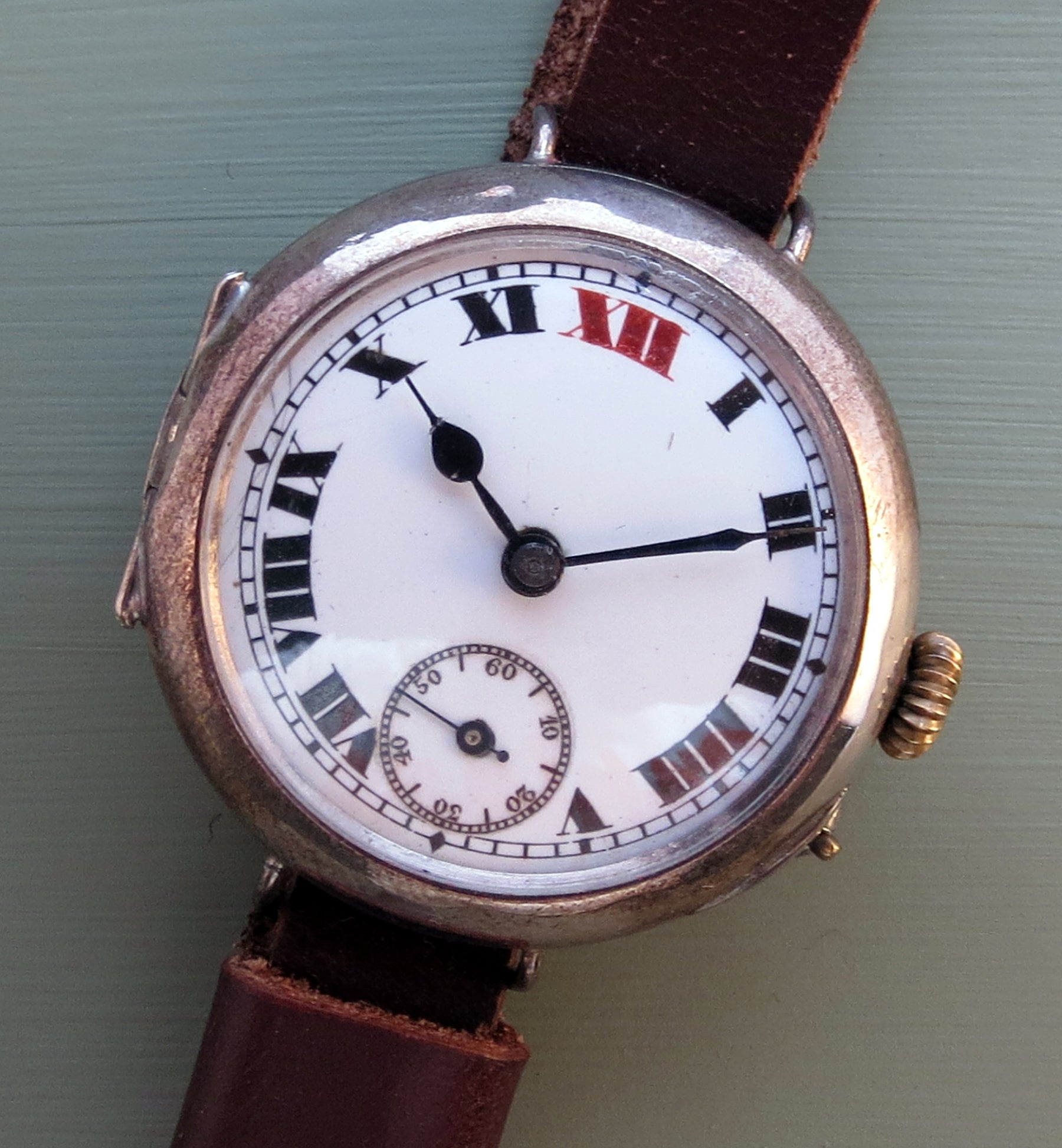 "Early trench watch in sterling silver with a 1914 hallmark. Note the enamel, the red 12 and the absence of luminous paint. The pin at 4 O'clock has to be depressed to allow the time to be set, a so called ""pin-set"" movement."