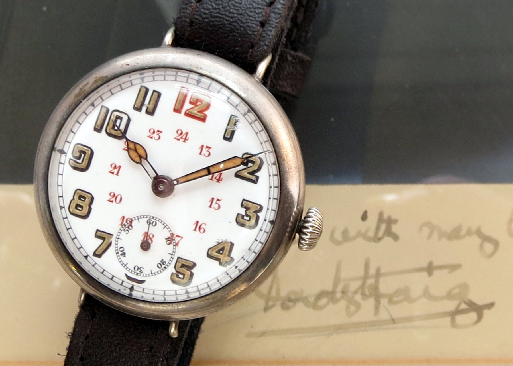 "Later WWI trench watch in sterling silver hallmarked for 1917. Note the luminous numerals and ""Cathedral hands"" together with 24 hour ""military time"" numerals. Signature of Field Marshall Douglas Haig, Commanding Officer of the British Expeditionary Force on the Western Front, in the background for the eagle eyed!"