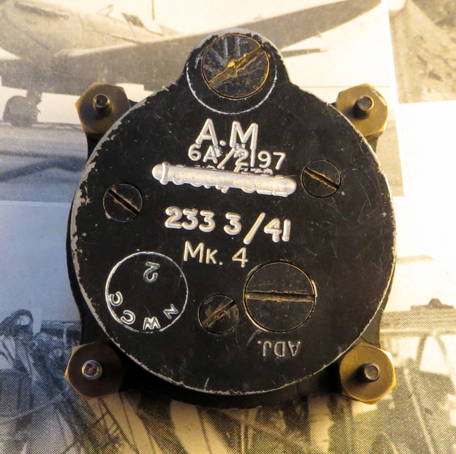 "Reverse of 8-day cockpit clock. Note the markings on the back ""A.M."" stands for Air Ministry and ""41"" for 1941, the year of issue. The original serial number has been crossed out and re-engraved, possibly after it was reused in a different aircraft. Incredibly, even though it is nearly 80 years old this particular one is still accurate to within 3 seconds per day, and only needs to be wound once a week."