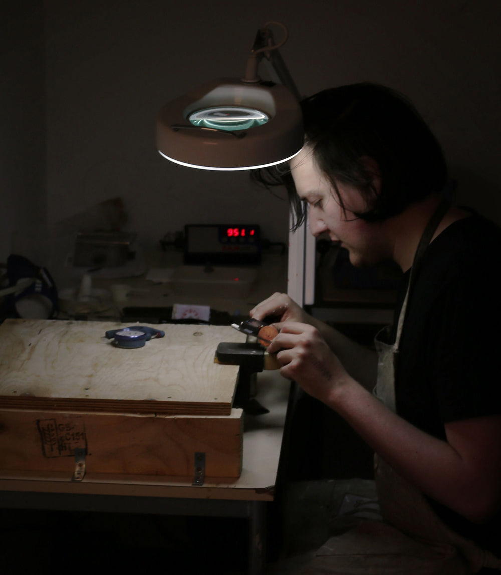 Adam at work sanding down a dial blank in our Glasgow workshop