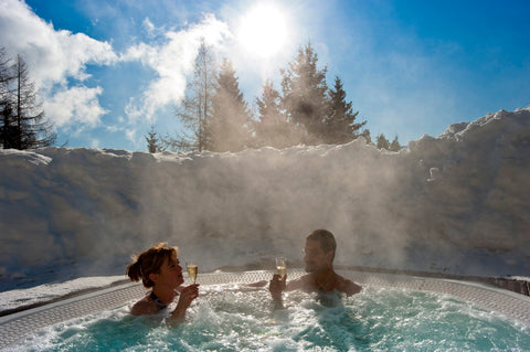 Image of a couple enjoying a glass of white wine in a hot tub surrounded by sunshine and snow