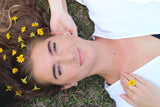 flowers in her hair and flower earrings and necklace