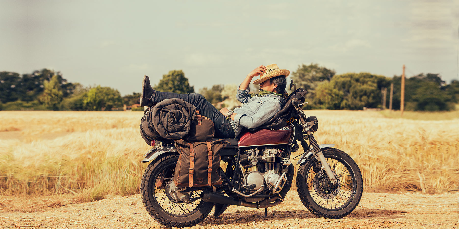 Biker sleeping on retro motorcycle with soft saddlebags.