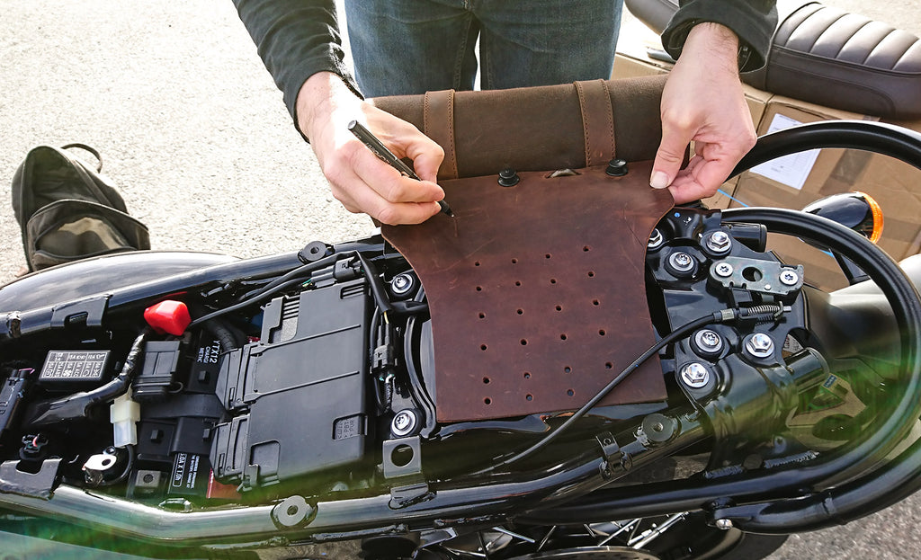 Man fitting a leather luggage support on the Bonneville motorcycle.