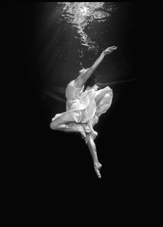 poster with a ballerina in a dress, dancing below the water surface